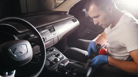 detailing : Car service. A young man polishing a car panel with an automatic brush