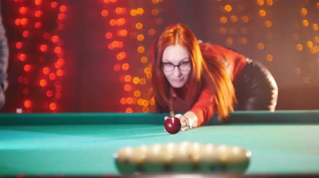 устроенный : Concentrated ginger woman playing billiard in billiard club. Breaks down arranged balls