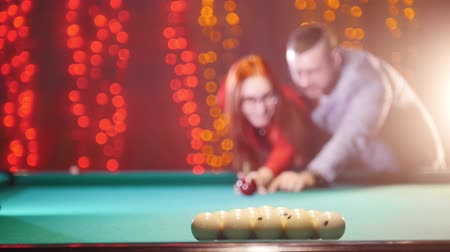sinuca : A couple playing billiards. A woman breaks down arranged balls