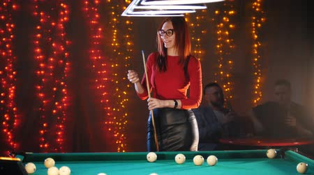 imbir : An attractive woman standing in billiard club rubbing chalk on a cue, while two men drinking beer on the background