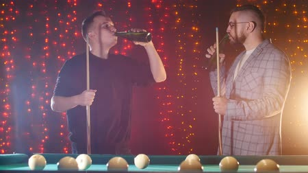 sinuca : Two men standing by the billiards table holding a cue and drinking beer. Cheers Stock Footage