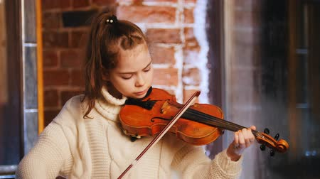podfuk : A little girl in white sweater playing violin