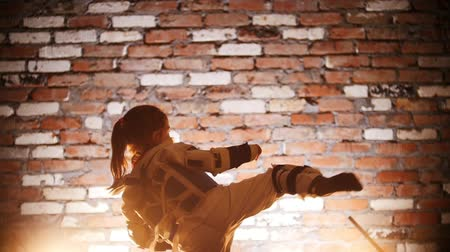 pózy : Training studio. Martial arts. A little girl balancing on one leg and kicking the air