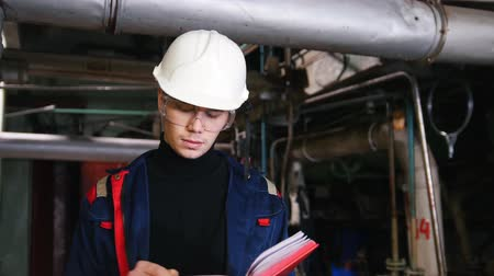 inspector : A man engineer in a helmet and protective glasses making notes in manufacturing plant
