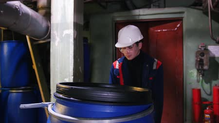 barril : A man engineer wearing a helmet in manufacturing plant rolls a cart with an empty barrel Stock Footage
