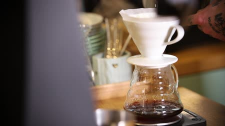 another : Barista making coffee americano in alternative method using a funnel