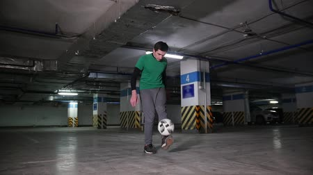 талант : A young man performing professional football tricks on the underground parking