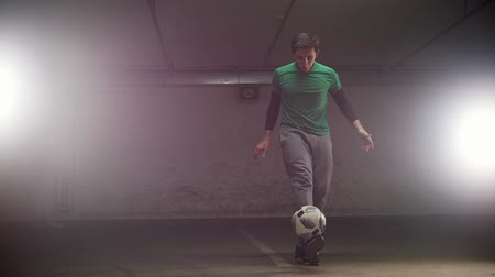 tekmeleme : Underground parking. A young soccer man training football tricks. Balancing the ball on the foot