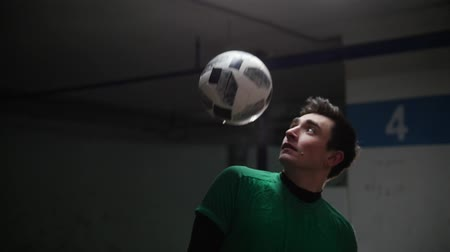 isabet : A young soccer man training football tricks. Hitting the ball with a shoulders