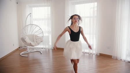 sitting floor : Young beautiful woman ballerina in glasses runs up and jumps performing a split in the air