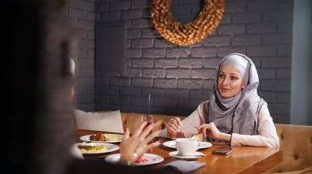 żart : A young muslim women sitting in a cafe, talking and laughing