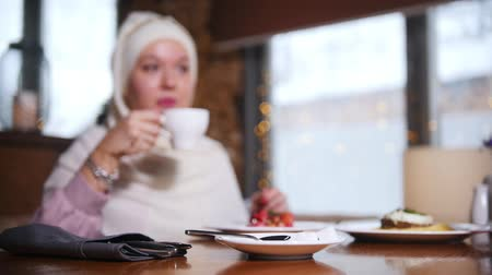 официант : A young muslim woman sitting in a cafe and sipping coffee