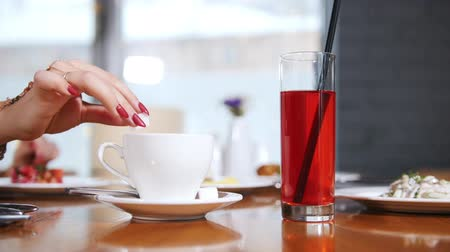 латте : A cup of coffe and a glass of drink on the table. A woman hand takes the sugar and put it in the cup, another woman touches the straw. Takes the drinks closer Стоковые видеозаписи