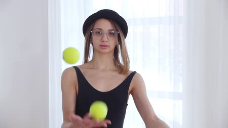 baletnica : Young woman in glasses juggling with a tennis balls Wideo