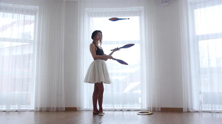 cyrk : Young woman ballerina performs circus juggling standing near the window