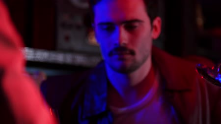 öykü : Bar with neon lighting. Company of friends drinking beer. A puzzled man with a mustache