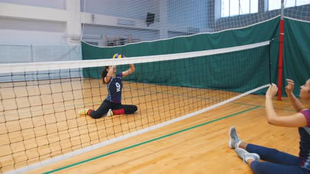 volleyball players : Sports for disabled people. Two young women sitting on the gym floor and playing volleyball Stock Footage