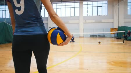 röplabda : Sports for disabled people. A young woman trainer walks to her ward holding a volleyball ball and sit down on the floor Stock mozgókép