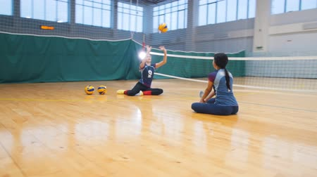volleyball players : Sports for disabled people. Two young women sitting on the floor in the gym and playing with a ball Stock Footage