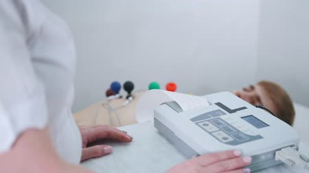 indicating : A medical clinic. A man receiving a ECG procedure. A results tape coming out of machine