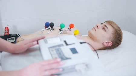 nadciśnienie : A man receiving a ECG procedure. A results tape coming out of machine Wideo