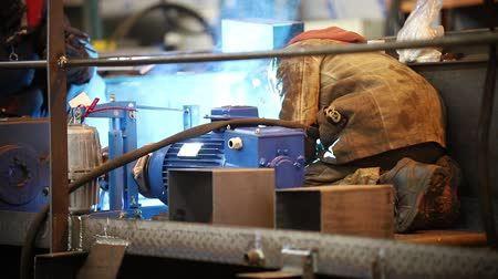metallurgical plant : Industrial concept. A man welder in dirty work clothes working on a plant