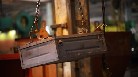 metallurgical plant : Industrial concept. An industrial lifting crane with a chain on holding a metal box