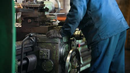 metallurgical plant : Industrial concept. Construction plant. A man worker making a detail on a lathe on electronic machine