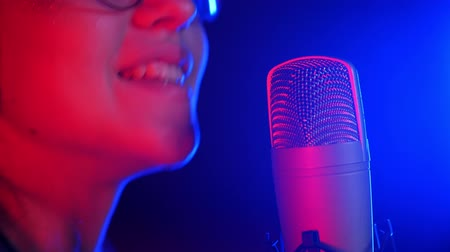 наушники : A young smiling woman in headphones singing in the studio. Neon lighting
