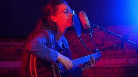 osvětlovací zařízení : A young woman in glasses playing guitar and singing song in neon lighting