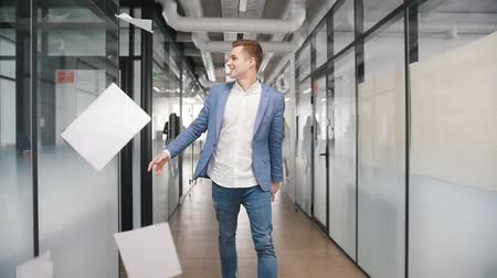 motiviert : An excited businessman dancing in office corridor and throwing papers in the air