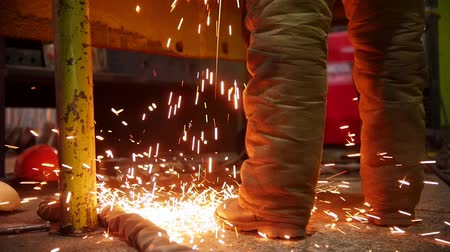 metallurgical plant : Construction plant. A fire sparkles falling on the floor near the worker Stock Footage