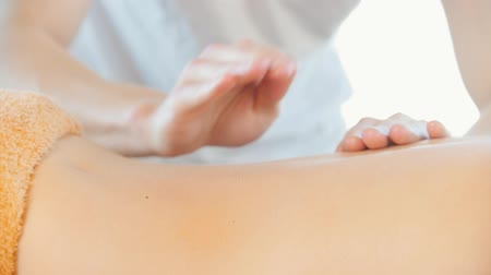 terapeuta : A young woman receiving a relaxing back massage. A masseur making a tapping motions