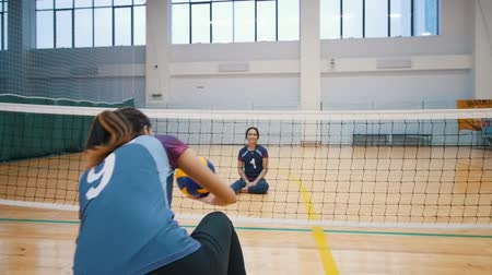 усилие : RUSSIA, KAZAN. 09-02-2019: Sports for disabled people. A young woman trainer walks to her ward, sit down on the floor and starts playing volleyball Стоковые видеозаписи