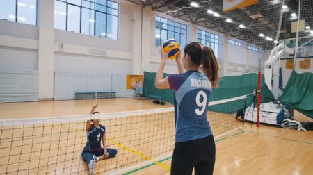 volleyball players : RUSSIA, KAZAN. 09-02-2019: Sports for disabled people. A young woman sitting on the floor and playing volleyball with her trainer standing up