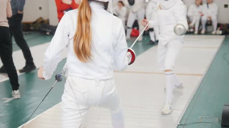 versengés : 27 MARCH 2019. KAZAN, RUSSIA: Teenage girls fencers in white protective clothes fighting on a fencing tournament Stock mozgókép