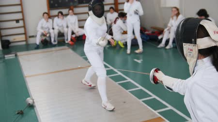 saber : 27 MARCH 2019. KAZAN, RUSSIA: Teenage girls fencers in white protective clothes training their fighting