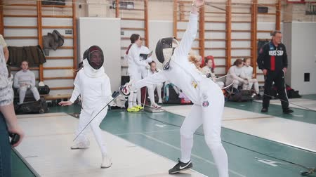 saber : 27 MARCH 2019. KAZAN, RUSSIA: Teenage girls in white protective clothes fighting on a fencing tournament in the school hall