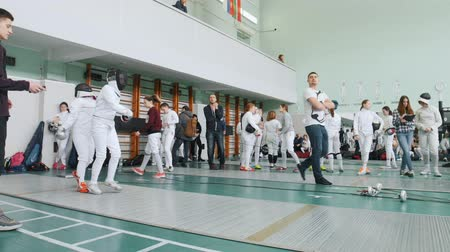 saber : 27 MARCH 2019. KAZAN, RUSSIA: Teenagers in protective clothes fighting on a fencing tournament in the school hall