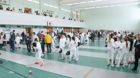 szermierka : 27 MARCH 2019. KAZAN, RUSSIA: A big tournament in the hall with many people. Teenagers fencers in protective clothes fighting Wideo