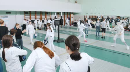 フェンシング : 27 MARCH 2019. KAZAN, RUSSIA: A big tournament in the hall with many people. Teenage girls fencers are getting ready for the round