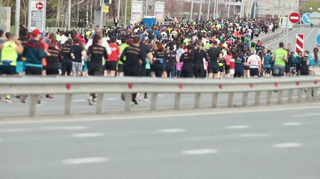 быстрый : 05-05-2019 RUSSIA, KAZAN: A running marathon. A big crowd of people are involved running on the road behind the fence Стоковые видеозаписи