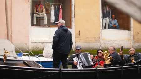kano : 29-04-2019 ITALY, VENICE: A man guide people on the boat on a water channel in Venice. Another man playing accordion