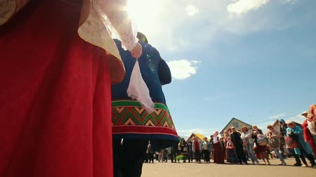 zsebkendő : RUSSIA, Nikolskoe village, Republic of Tatarstan 25-05-2019: A women in traditional russian clothes standing in front of the crowd and dancing waving a handkerchief. A man playing accordion Stock mozgókép