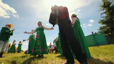 刺繍 : RUSSIA, Nikolskoe village, Republic of Tatarstan 25-05-2019: An old women in traditional clothes standing on the field and dancing by accordion music singing chastooshkas
