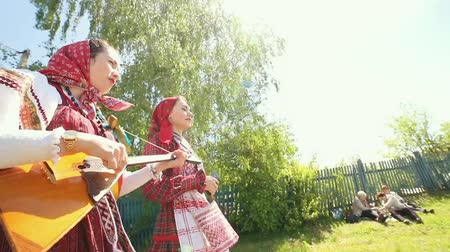 zsebkendő : RUSSIA, Nikolskoe village, Republic of Tatarstan 25-05-2019: Two young women in traditional russian clothes walking on the road in the village and singing a song playing a balalaika Stock mozgókép
