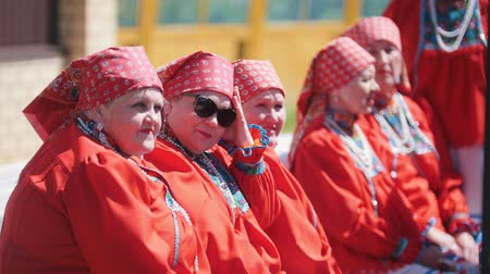 groupe : Tatarstan, Laishevo 25-05-2019: Women in red traditionally Russian attire sit on the bench. Stock Footage