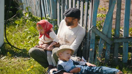 groupe : Tatarstan, Laishevo 25-05-2019: A man with his daughter and son is sitting by the fence, then his wife approaches him.