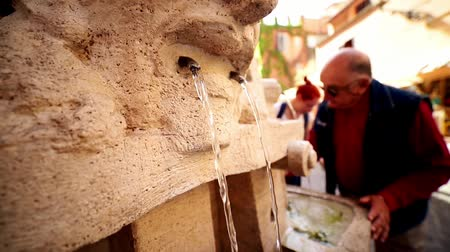 drinking water supply : 19-04-2019 ROME, ITALY: Man drinking water from fountain sculpture
