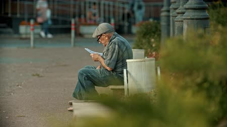 lixeira : KAZAN, RUSSIA - 14 JULY 2019: An old man sitting on a bench and reading a book Vídeos